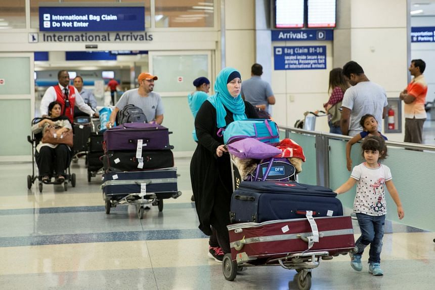 People come through the international arrivals gate from Dubai at Dallas/Fort Worth International Airport.