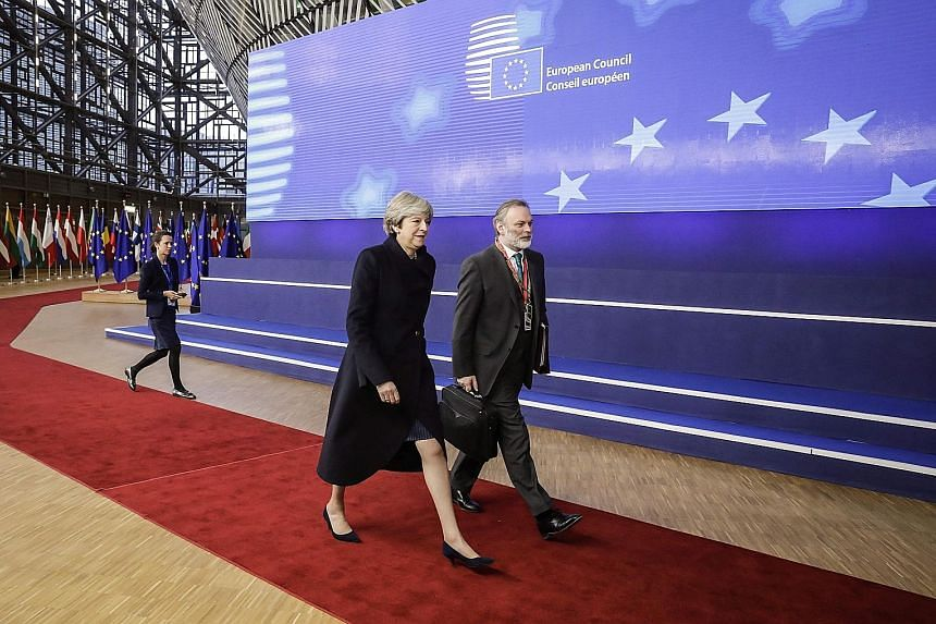 Britain's Prime Minister Theresa May and UK Permanent Representative to the European Union Tim Barrow arriving for the first day of an EU summit in Brussels on Thursday. The bloc agreed yesterday to move talks forward with London.