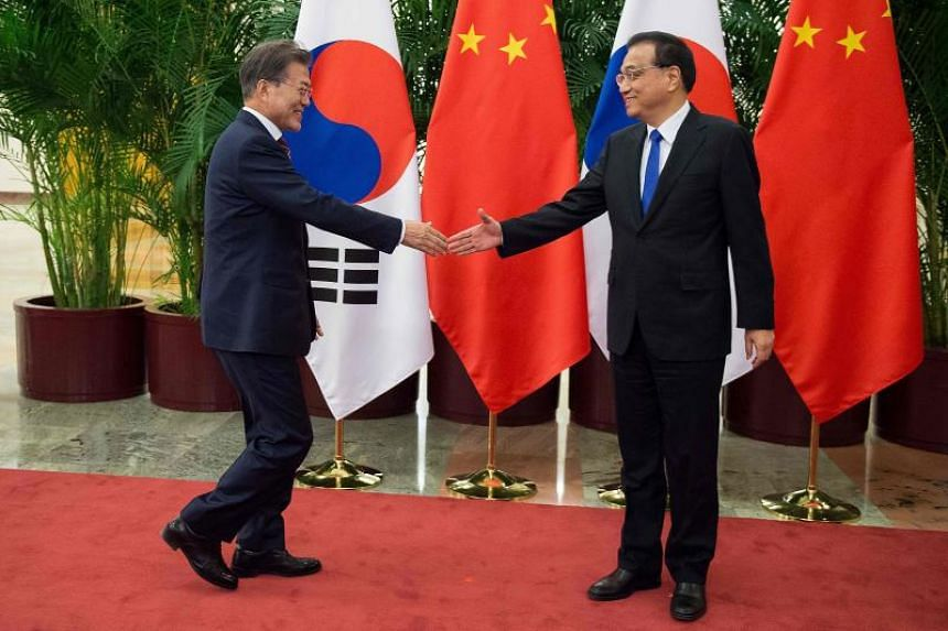 South Korean President Moon Jae-In (left) shake hands with China's Premier Li Keqiang (right) at the Great Hall of the People in Beijing on Dec 15, 2017.
