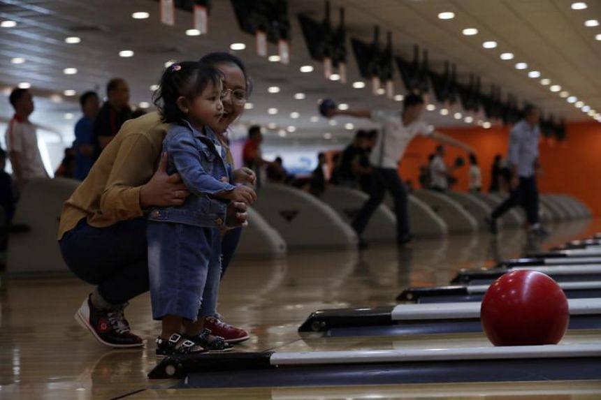 Eight-month-old Sofea Erica receives guidance from her aunt Dafinah during a game.