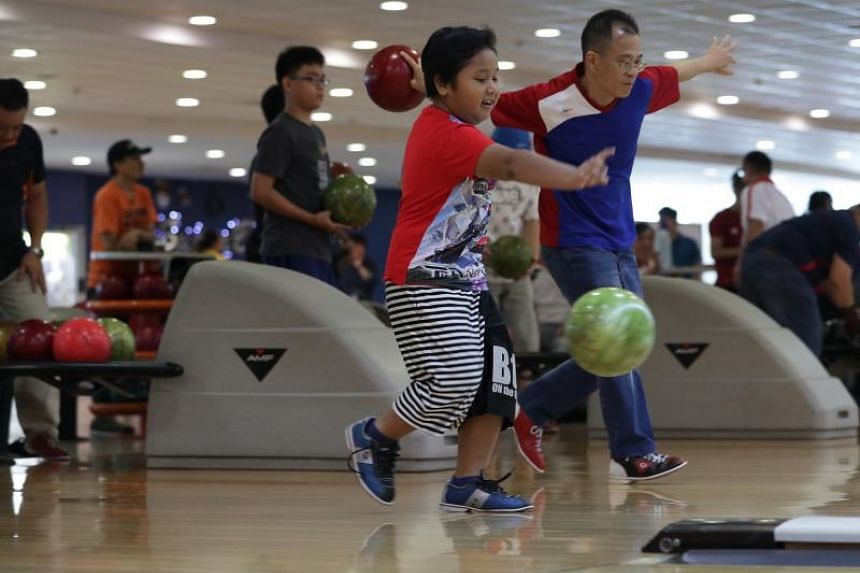 Eight-year-old Yusrizqi Laziqriy, one of the beneficiaries of The Straits Times School Pocket Money Fund, take part in the game.