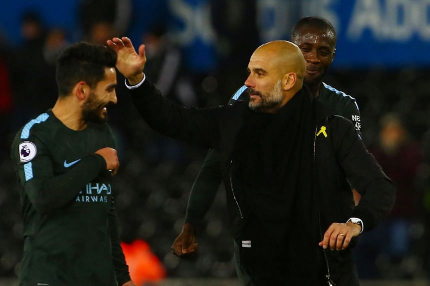 Manchester City's manager Pep Guardiola (right) greets his players after winning the match between Swansea City and Manchester City, on Dec 13.