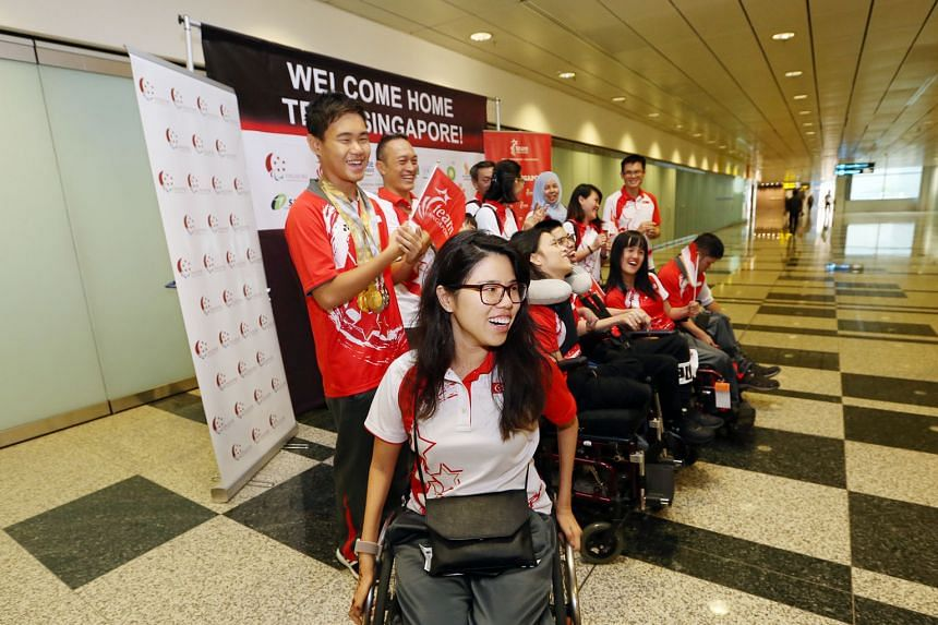 Returning home yesterday from the Asian Youth Para Games (AYPG) in Dubai were Singapore's most bemedalled athlete at the Games, para-swimmer Wong Zhi Wei (standing, far left) and Games chef de mission Yip Pin Xiu (front). Zhi Wei, 15, won three golds