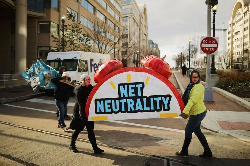 Rally organisers carry away props following a protest against the end of Net neutrality rules, on Dec 14.