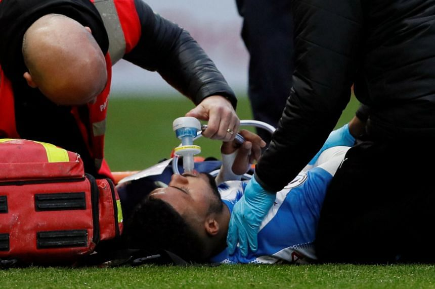 Huddersfield Town's Elias Kachunga scored before being carried off on a stretcher with a knee injury (above).