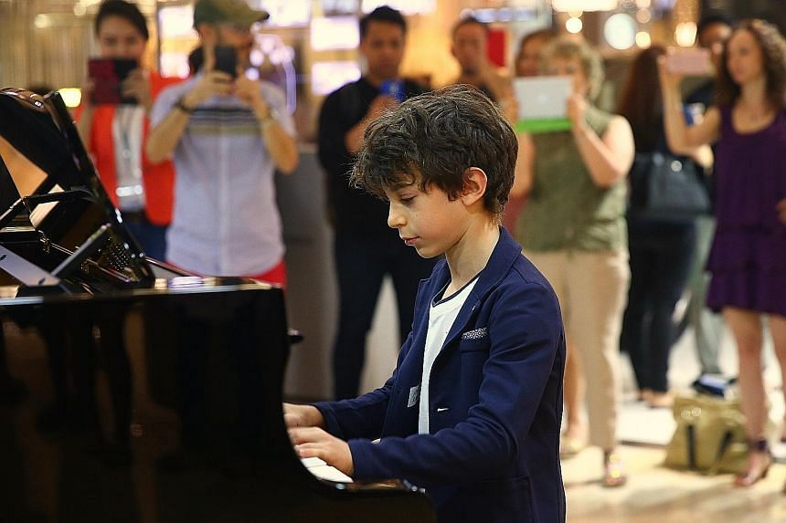 Eleven-year-old Jesse Collins playing his own composition in the piano marathon at Ion Orchard yesterday. Proceeds from the 13-hour charity marathon will go to The Business Times Budding Artists Fund, which provides arts training to young people from