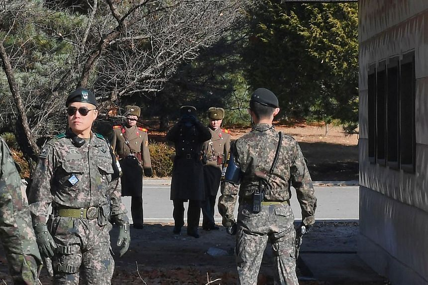 North and South Korean soldiers at the truce village of Panmunjom. The North Korean defector who made a dash last month was shot while fleeing across the border.