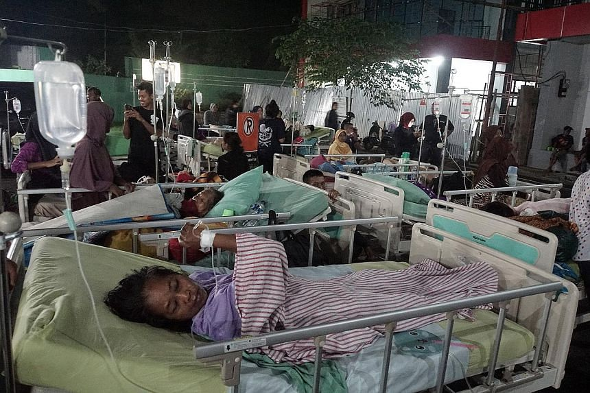 Left: A man going through the rubble of his collapsed house yesterday after a 6.5-magnitude earthquake hit Sumelap Village in Tasikmalaya, West Java, just before midnight on Friday. Below: Patients in Banyumas' regional public hospital in Central Jav