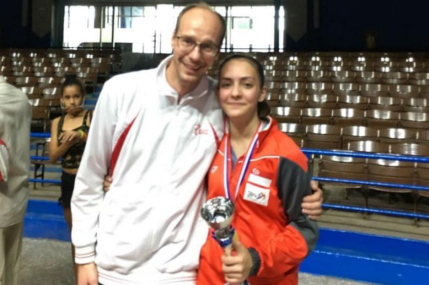 Singapore's foil fencer Amita Berthier (right), poses with coach Ralf Bissdorf after winning the Junior World Cup title in Havana. The 17-year-old is the first Singaporean to win a title in the eight-leg series.