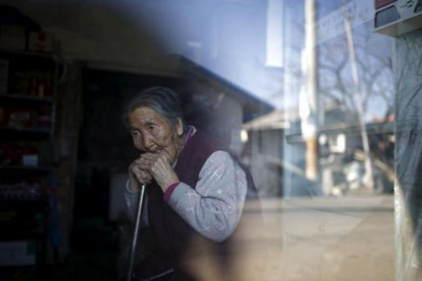 An elderly woman sits inside a small store at a village in South Korea.