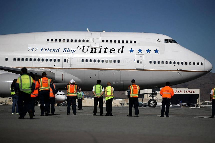 United Airlines workers look on as United Airlines flight 747 prepares to take off from San Francisco International Airport for its final flight to Honolulu, on Nov 7, 2017.