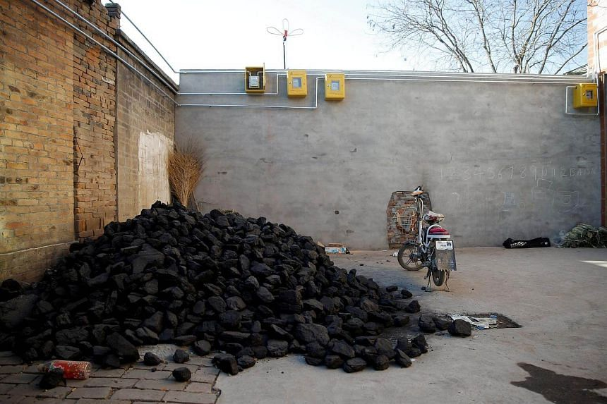 A pile of coal lies underneath newly installed gas pipes in a courtyard in Heqiaoxiang village, Hebei province. China's attempts to get people to switch from coal to gas has been sputtering.