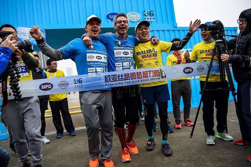 German management consultant Kai Markus (centre) being helped across the finish line by friends at the Shanghai International port on Dec 16, 2017.