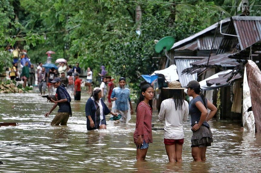 Villagers wade through a flooded street in Brgy Calingatngan, Borongan, on Dec 16, 2017, after Tropical Storm Kai-Tak pounded the eastern Philippines, cutting off power and triggering landslides.