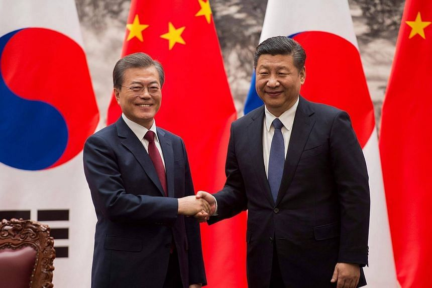 South Korean President Moon Jae In (left) and Chinese President Xi Jinping shake hands at the end of a signing ceremony at the Great Hall of the People in Beijing, on Dec 14, 2017.