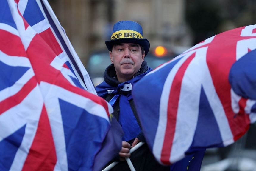 A pro-EU anti-Brexit demonstrator waves EU and British flags outside the Houses of Parliament in London.