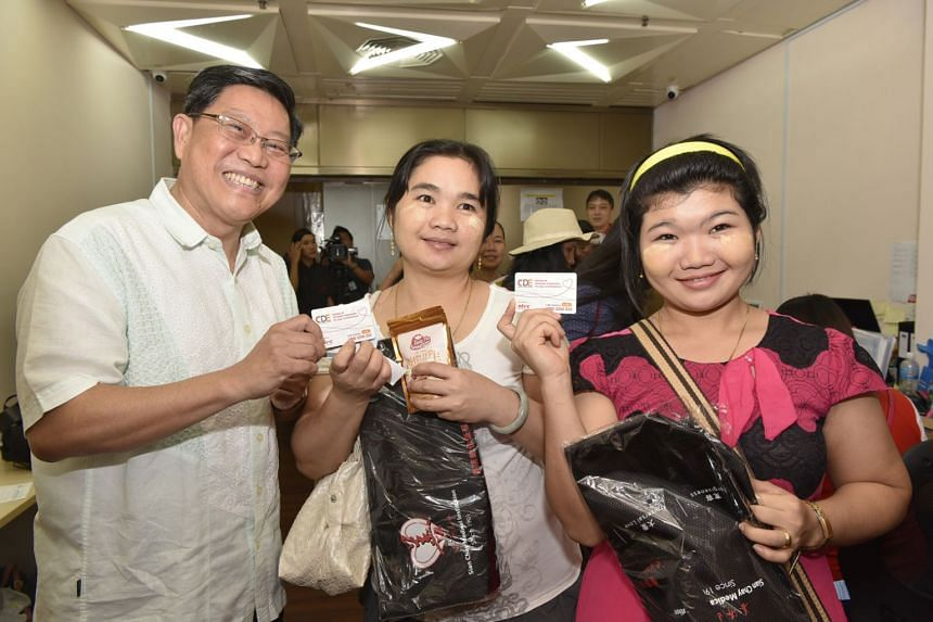Centre for Domestic Employees chairman Yeo Guat Kwang, with Mya Mya That and her sister, Nae Jae May, both domestic workers from Myanmar, at an event to celebrate International Migrants Day on Dec 17, 2017.
