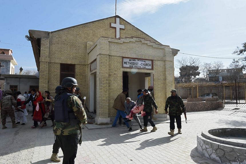 Pakistani security personnel rescue an injured woman after suicide bombers attacked a Methodist church during a Sunday service in Quetta on Dec 17, 2017.