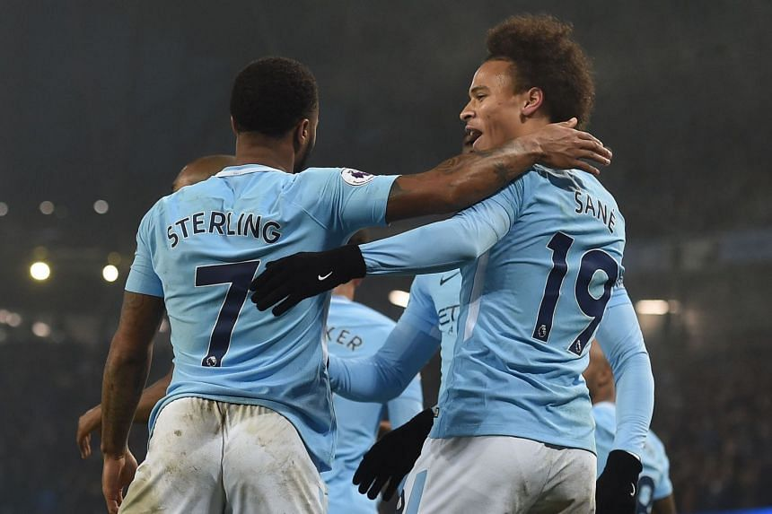 Manchester City's Raheem Sterling celebrates scoring their third goal with Leroy Sane.