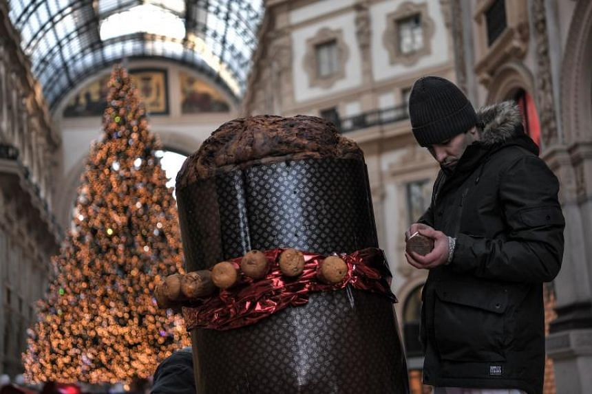 A baker decorates a giant Panettone on Dec 17, 2017 in the Vittorio Emanuele II gallery in Milan. The Panettone, a typical brioche of Christmas in the Lombardy region, is traditionally stuffed with raisins, candied fruits and citrus zest.