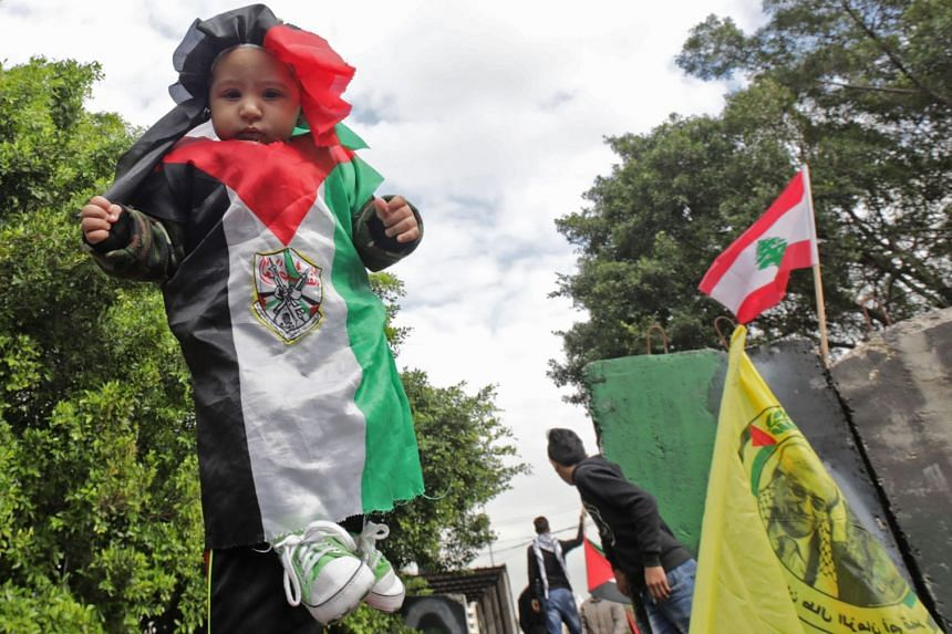 A Palestinian girl dressed in the colours of the national flag with Fatah's emblem is held up during a protest against Donald Trump's Jerusalem move.