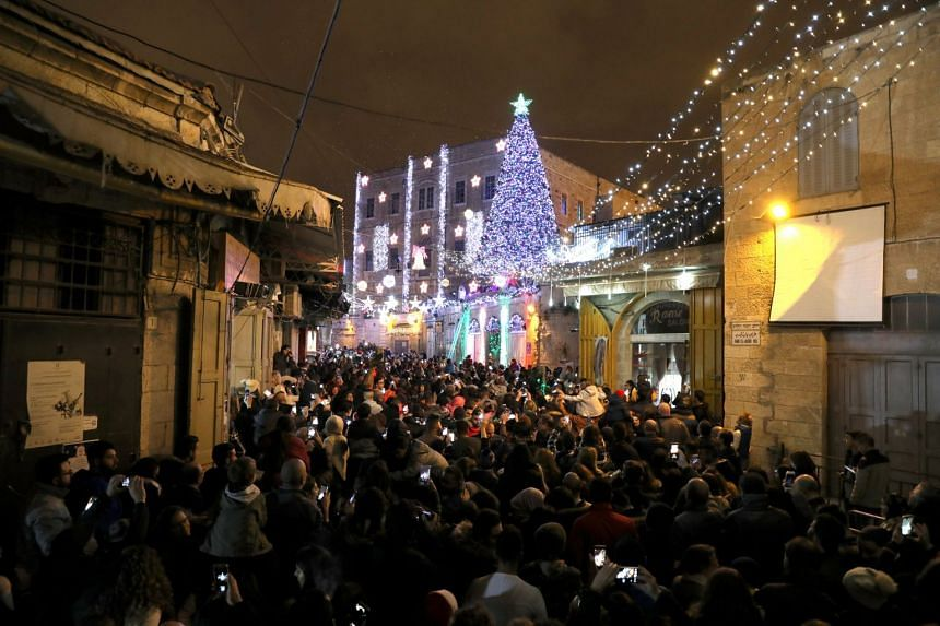 People attending a Christmas tree lighting ceremony in Jerusalem's Old City last Thursday. The city attracts thousands of pilgrims at Christmas every year.