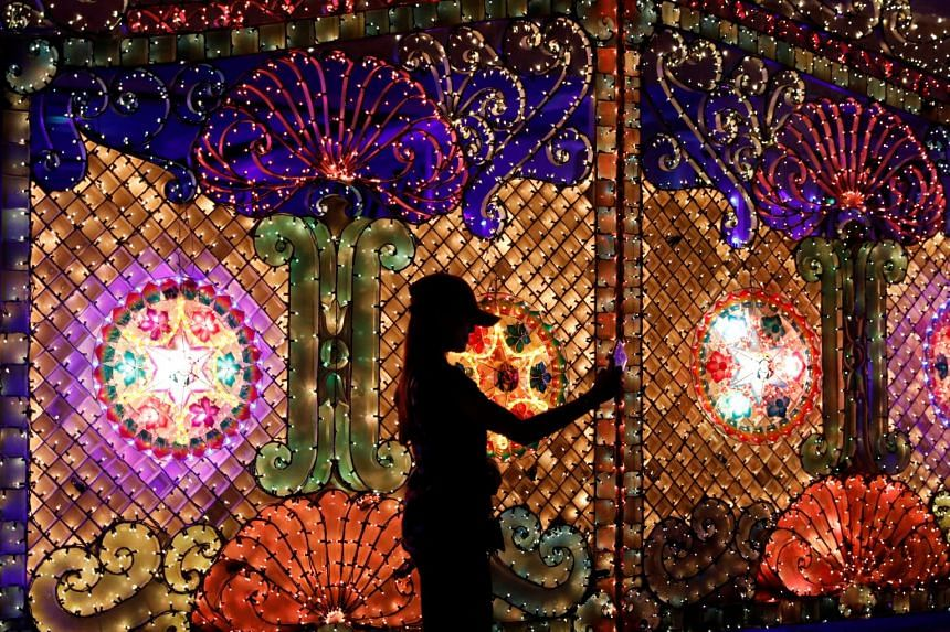 A girl taking a selfie in Policarpio Street in Mandaluyong, Philippines. The houses there are usually covered in lavish decorations during this season.