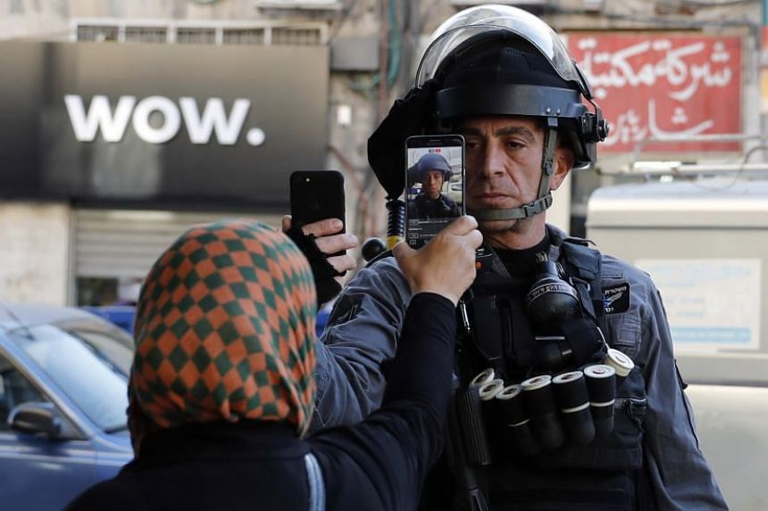 A Palestinian woman takes a picture of a member of the Israeli security forces as he takes her picture in a street in Jerusalem, as demonstrations continued to flare in the Middle East and elsewhere over the US president's declaration of Jerusalem as