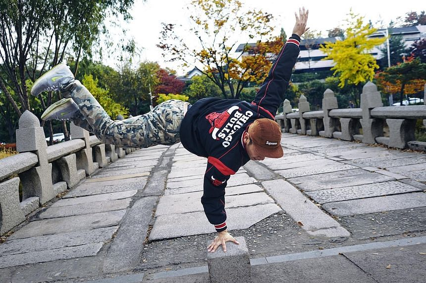Hong Sung Jin, a member of the South Korean Gamblerz crew who goes by the moniker Pop, shows off a move. Break-dancer Park Woo Sang from Fusion MC strikes a pose in a market in Seoul.