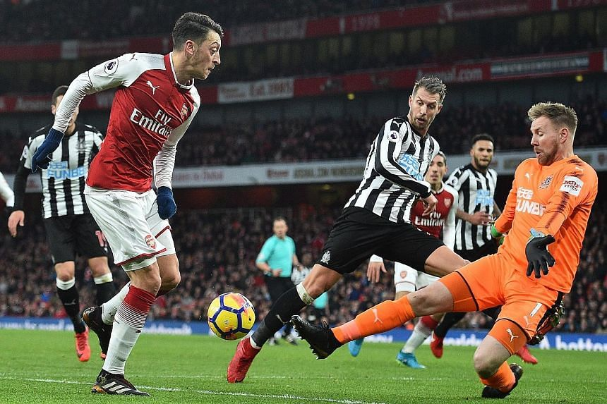 Arsenal midfielder Mesut Ozil (left) taking on Newcastle goalkeeper Rob Elliot on Saturday. Ozil scored the only goal of the Premier League match to end the Gunners' sequence of three games without a win.
