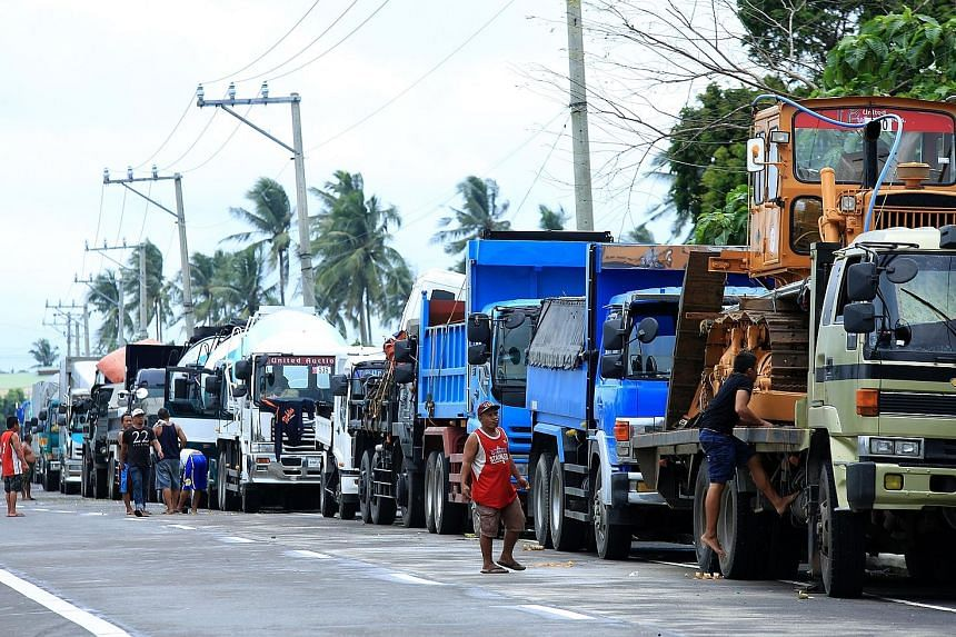 A long line of vehicles on a highway heading to the port in Matnog, Sorsogon, yesterday. Ferry services remained suspended, stranding thousands of people heading home for Christmas. A resident stands amid the damage after Tropical Storm Kai-Tak yeste