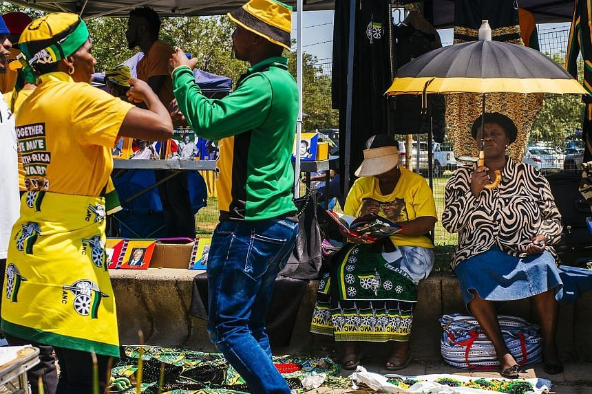 Supporters of South Africa's African National Congress (ANC) at a stall during the party's 54th national conference in Johannesburg yesterday. Thousands of ANC delegates began electing their next leader in a vote seen as a key moment in the country's