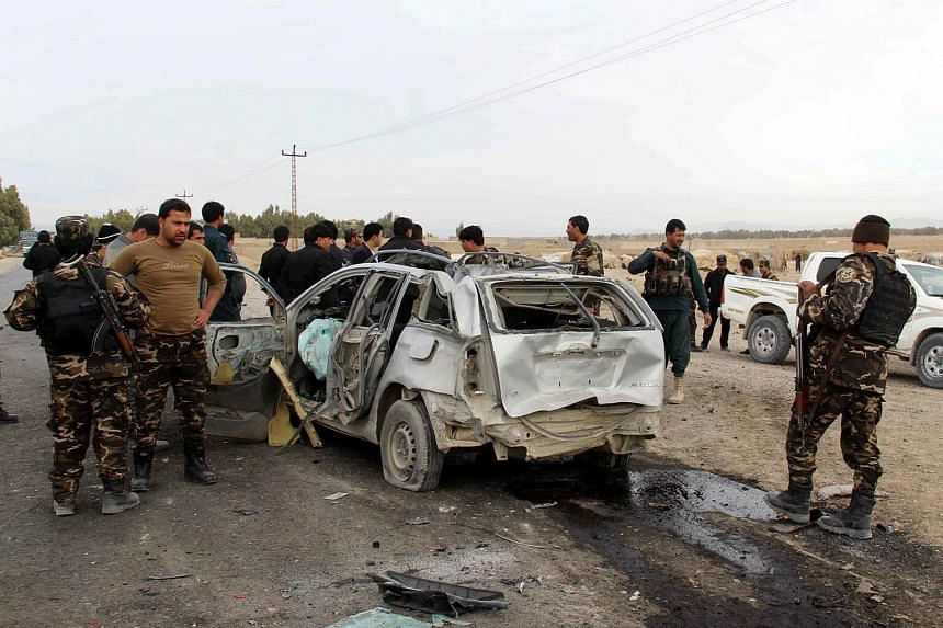 Security officials inspect the scene of a suicide bomb attack that targeted a convoy of foreign forces in Kandahar, Afghanistan, on Dec 17.