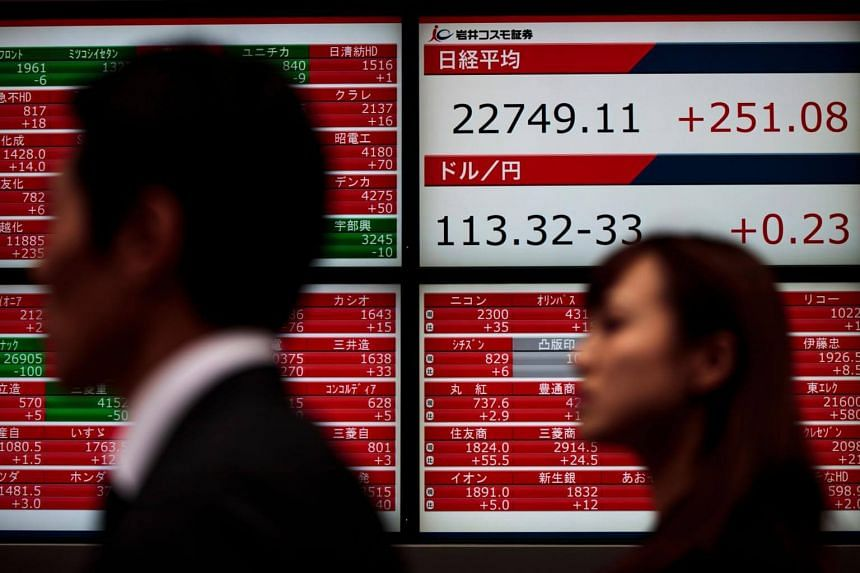 Pedestrians walk past a stock quotation board flashing the Nikkei 225 key index of the Tokyo Stock Exchange in Japan, on Dec 8, 2017.