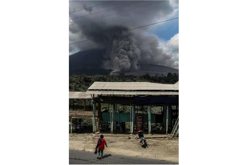 An Indonesian woman goes about her chores as the volcano spews thick ash in Karo, North Sumatra, on Dec 18, 2017.