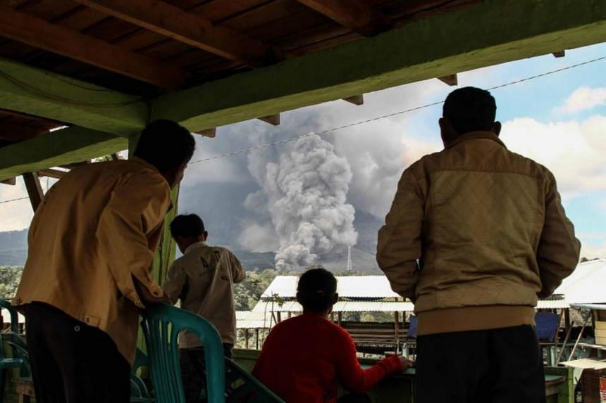 Indonesian villagers gather to watch the volcano spew thick ash.