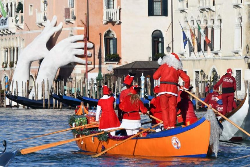 People dressed as Santa Claus take part in a regatta on the Grand Canal of Venice on Dec 17, 2017.