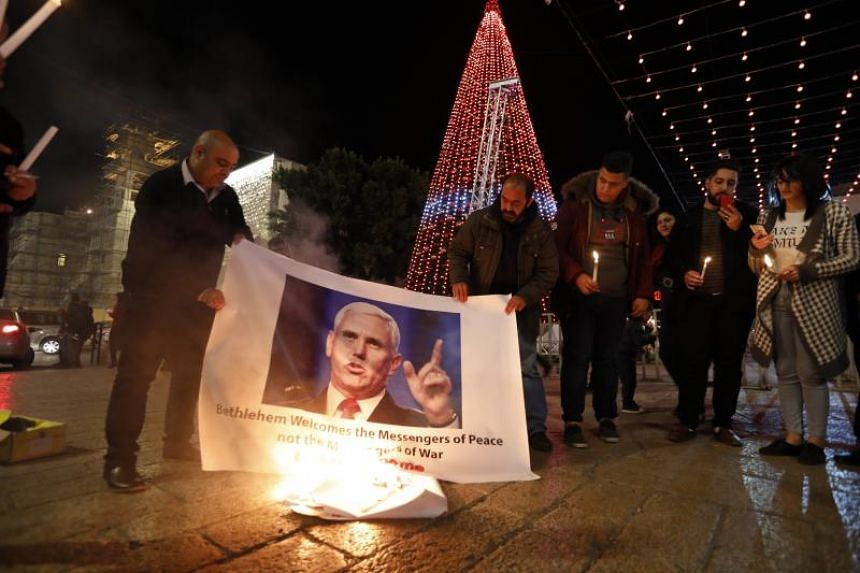 Palestinians burn the picture of the US Vice President Mike Pence during a protest against US President Donald Trump's decision to announce Jerusalem as the capital of Israel and the visit of Pence in the West Bank city of Bethlehem, on Dec 17, 2017.