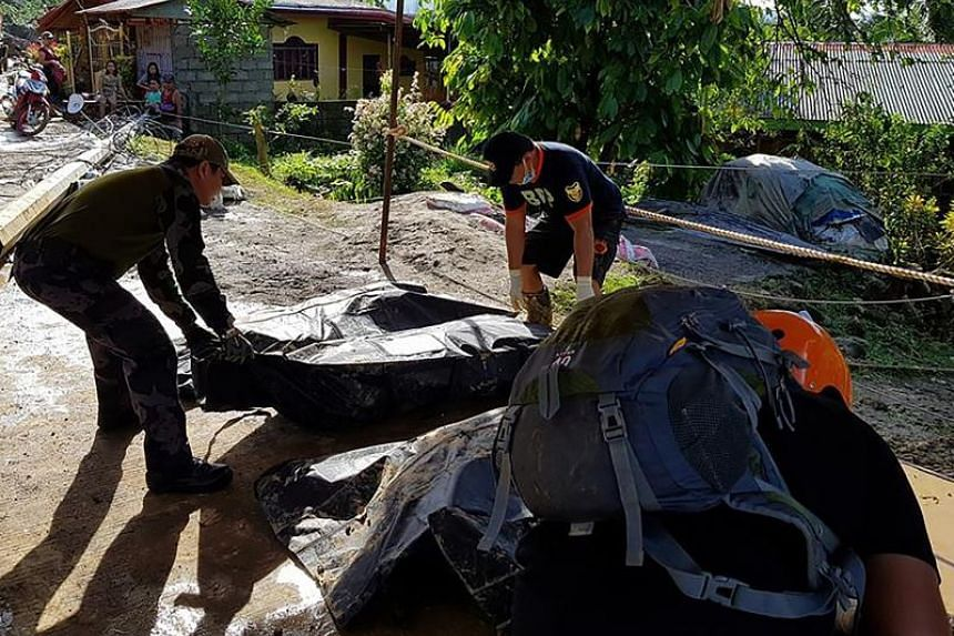Rescuers carry a body bag containing the body of a resident killed by a landslide following heavy rains triggered by Tropical Storm Kai Tak in the town of Naval, in Biliran province, Philippines.