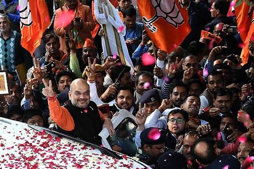 Bharatiya Janata Party president Amit Shah showing the victory sign to supporters in New Delhi yesterday.