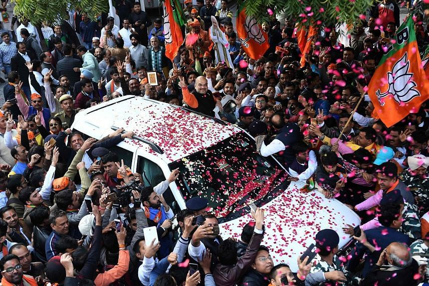 Bharatiya Janata Party president Amit Shah waving to supporters from his car as he arrived to address a press conference at the party's headquarters in New Delhi yesterday.