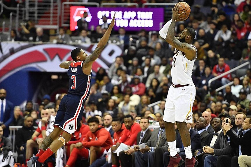 Cleveland forward LeBron James shooting a three-point basket as Washington guard Bradley Beal tries to defend. The Cavaliers won 106-99.