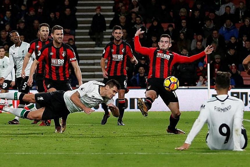 Dejan Lovren scoring Liverpool's second goal with a diving header in their 4-0 Premier League victory over Bournemouth on Sunday. The away win pushed the Reds back into the top four.