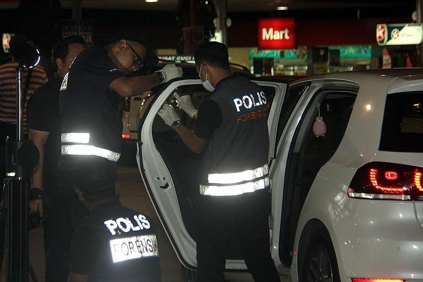 Officers from the forensic unit checking the car owned by a 44-year-old man who died after he was stabbed and then run over twice by four assailants in a BMW at a Shell petrol station in Jalan Sri Pelangi on Sunday.