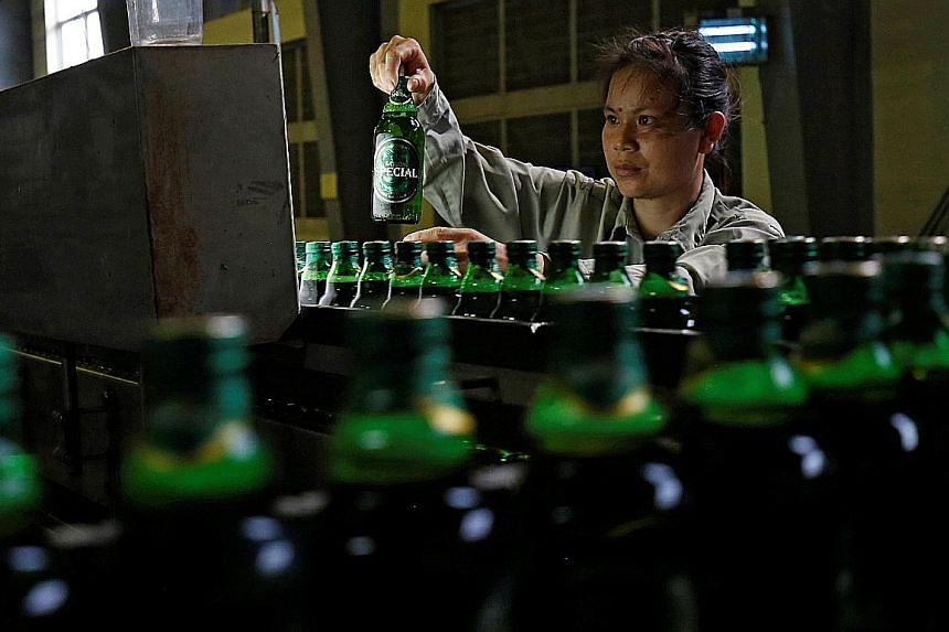 A worker checking beer bottles in a Saigon Beer Alcohol Beverage Corp factory. ThaiBev's deal gives it access to a strong player in Vietnam's thriving beer market, and will allow it to diversify its revenue streams.