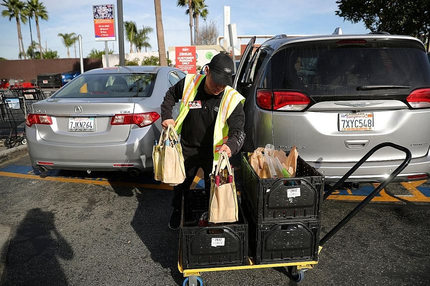 An employee from a Ralph supermarket in Los Angeles serving a customer who had ordered his groceries online and reserved a pickup time in advance.