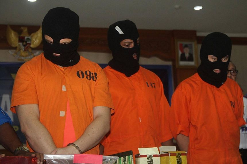 Drugs suspects Australian IER (left), American KSL (centre) and Malaysian CHJ are displayed by officials during a press conference at a customs office in Denpasar, on Dec 19, 2017.