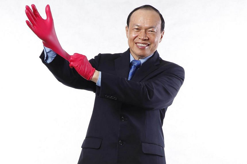 Executive chairmain of Top Glove Corporation Bhd Tan Sri Dr Lim Wee Chai poses with some gloves. The company's  net profit shot up 43.8 per cent to RM105.4 million (S$34.8 million) from the previous year.
