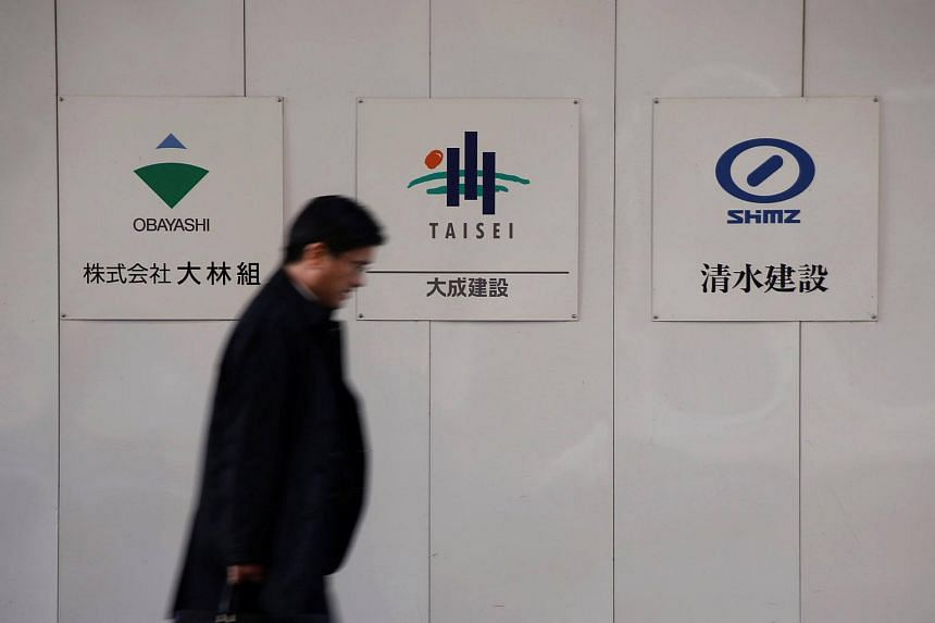 A man walks past logos of Obayashi Corp, Taisei Corp and Shimizu Corp outside a construction site in Tokyo, on Dec 18, 2017.