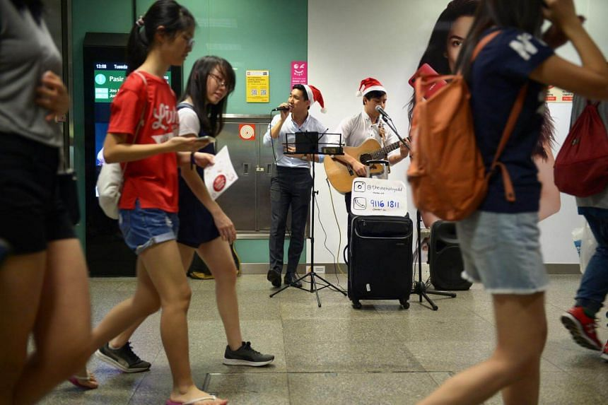 Buskers Ang Cheng Wei and Er Young Yee, perform at the Bugis MRT station on Dec 19, 2017.